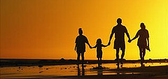 Image of family holding hands towards sunset