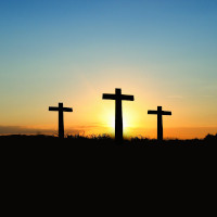 3 crosses on a hill - backlit by setting sun